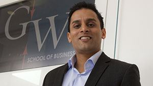 Dr. Sudip Bose posed in front of a GW School of Business plaque