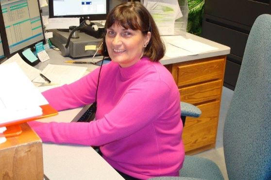 Smiling employee of the Public Safety Communications Center working at their desk