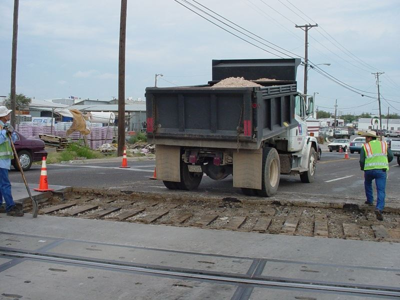 Street Department Workers Repave a Section of Road near Train Tracks